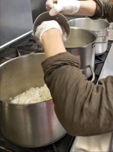 onions being added to the soup pots