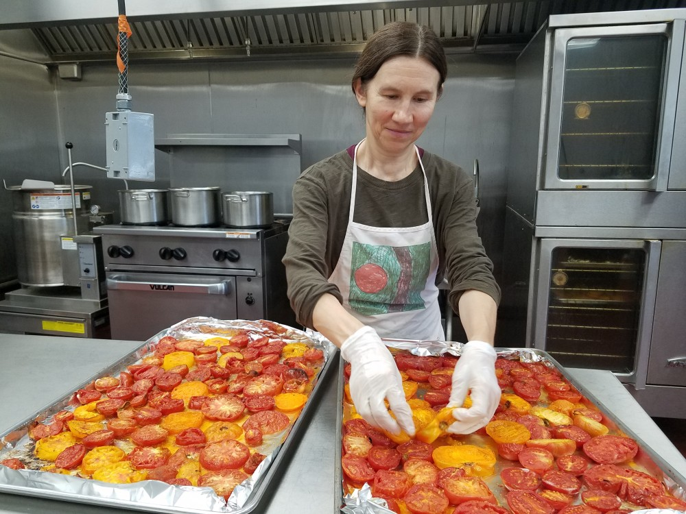 Julia with the pans of tomatoes ready to roast