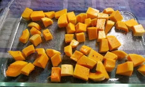 Butternut squash ready to roast in glass baking dish